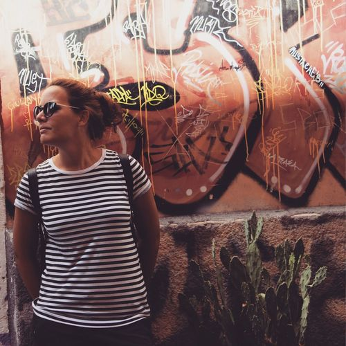 Woman In Sunglasses Standing Against Graffiti Wall