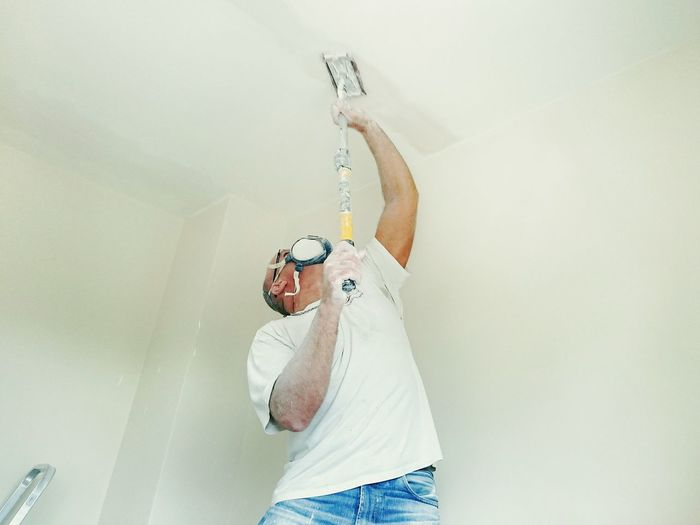 Man Painting Ceiling At Home