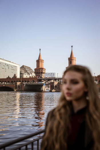 Portrait of woman with river in city