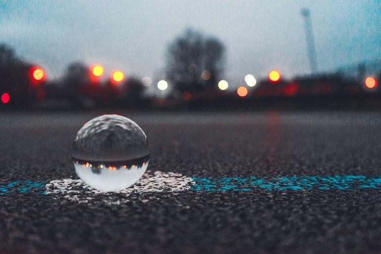 Marble on road against illuminated lights