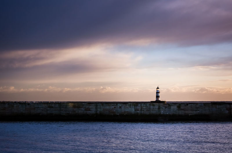 Lighthouse by sea against cloudy sky during sunset