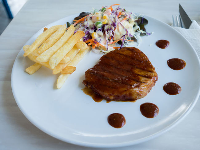 Pork chop with BBQ source. Grilled steak and salad. Baked BBQ Chop Close-up Cooked Dinner Dish Food Food And Drink Lunch Pork Potion Ready-to-eat Restaurant Roast Steak