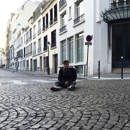 Full length portrait of man sitting on cobbled street by buildings
