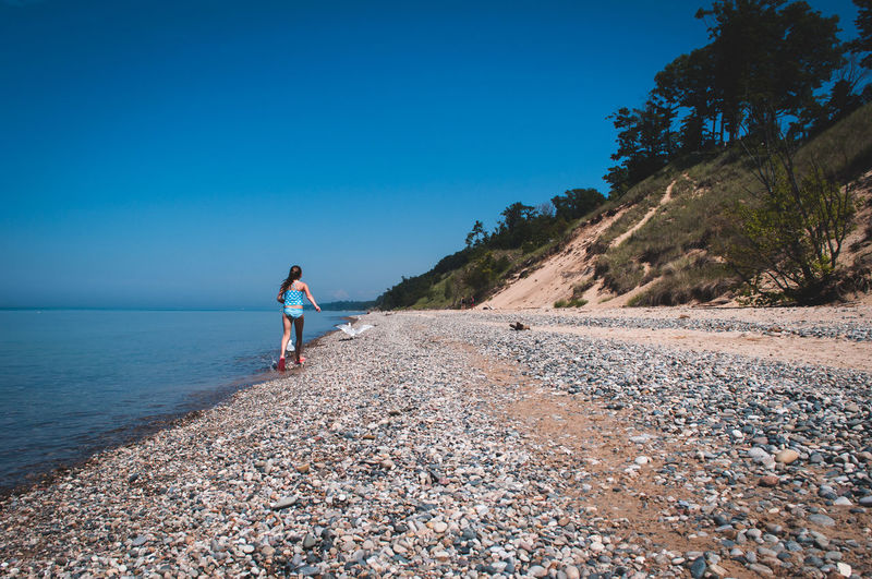 Girl Walking On Shore Against Clear Blue Sky