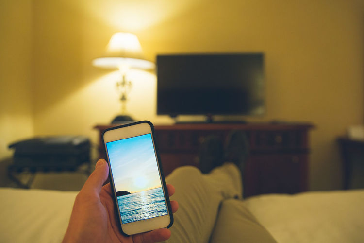 Hotel room escape Holding Hands Room Communication Connection Escape Escape From Reality Focus On Foreground Furniture Hand Holding Hotel Human Body Part Human Hand Indoors  One Person Photo Portable Information Device Real People Smart Phone Technology Wireless Technology