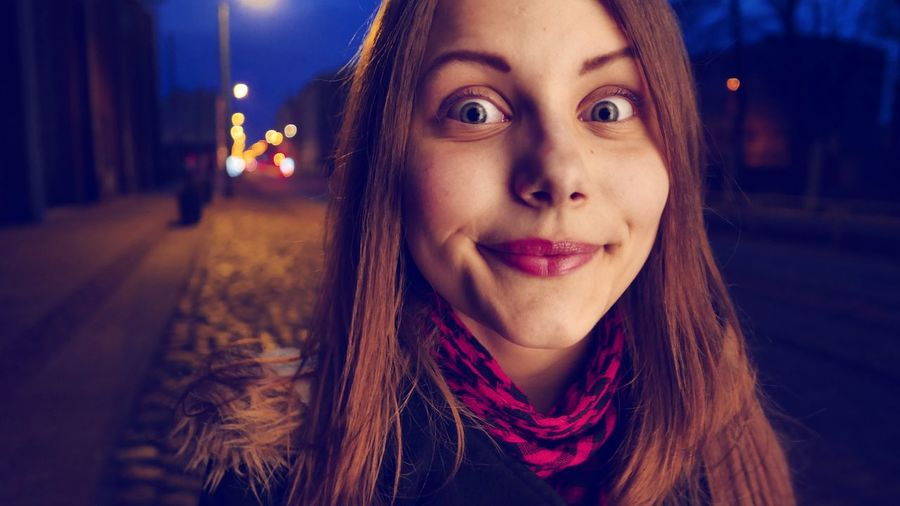 Close-Up Portrait Of Teenage Girl Smiling While Standing On Street At Night