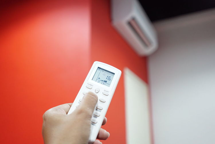 Cropped hand person operating air conditioner remote control