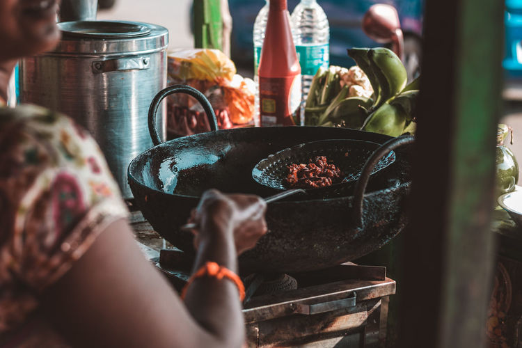 Midsection Of Woman Preparing Food At Stall