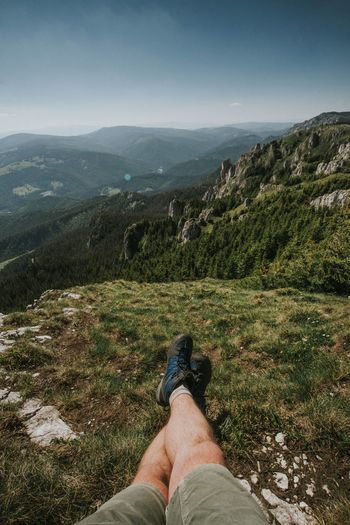 Low section of man on mountain against sky