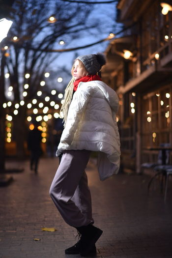 Woman in warm clothes while standing on sidewalk in city
