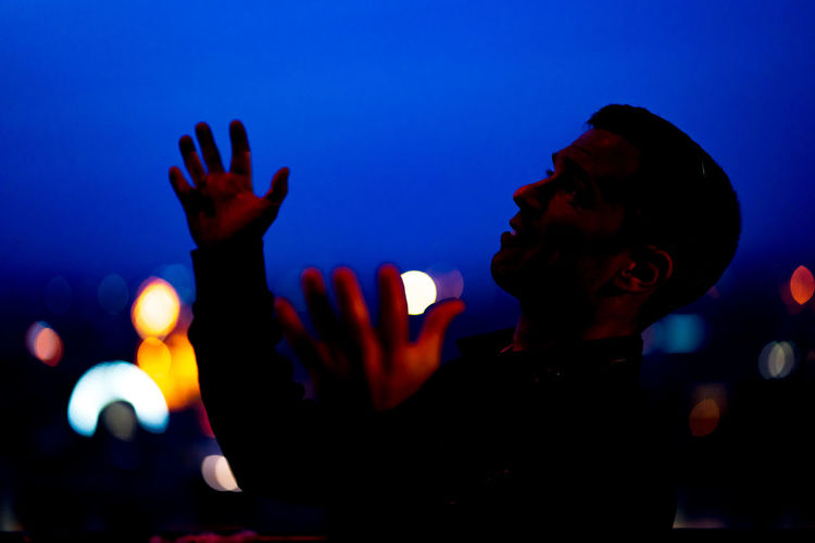 Close-up of silhouette man gesturing against clear blue sky at night