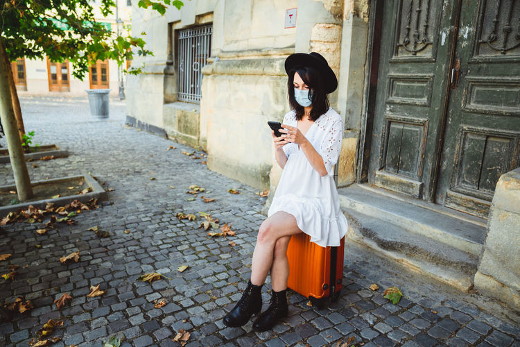 Full length of woman using mobile phone while sitting on footpath