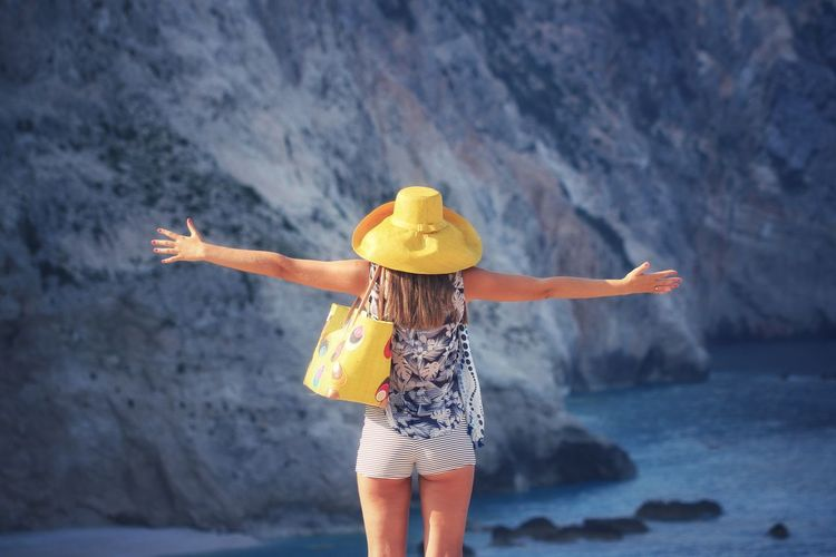 Woman in hat with arms outstretched standing against river