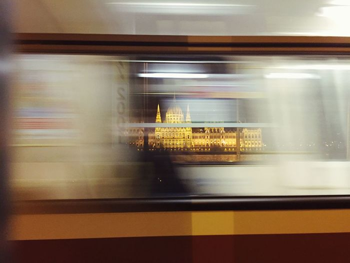 Blurred motion of subway train against illuminated hungarian parliament building