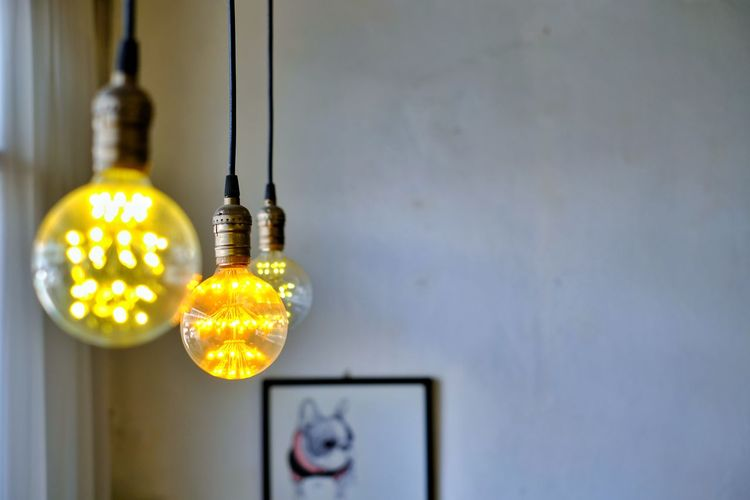 Close-up of illuminated light bulb hanging on wall at home