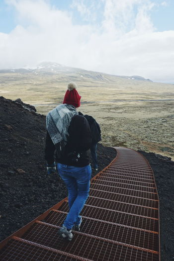 Rear view of woman walking staircase at volcanic mountain