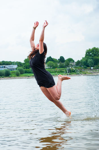 Young woman jumping over river against sky