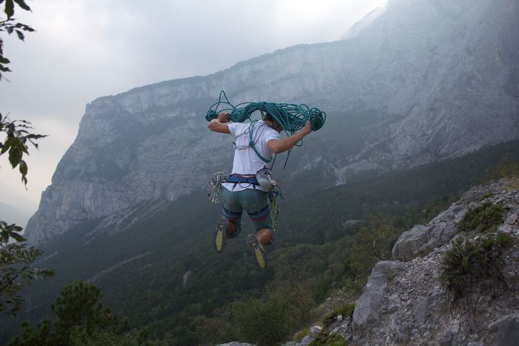 Rear view of man jumping with rope against mountain range