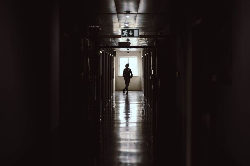 Rear view of silhouette woman standing in building corridor