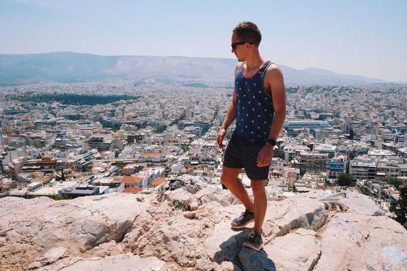 Man overlooking cityscape while standing on mountain during sunny day