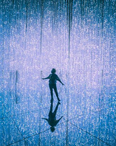 Full length of silhouette man walking against blue water