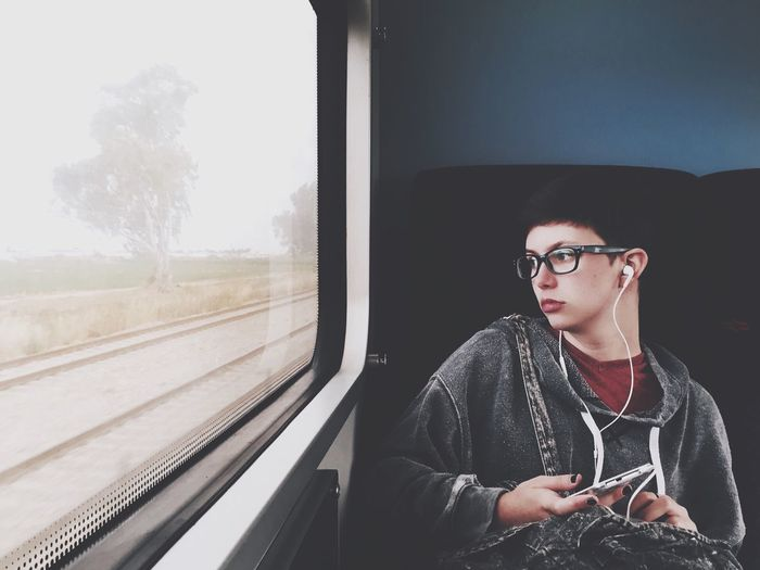 TakeoverMusic Eyeglasses  Sitting Young Adult Window One Young Man Only Indoors  Lifestyles Transportation One Person Front View Only Men Men One Man Only Day People Eye4photography  Mytrainmoments Mydtrainmoments Traveling Home For The Holidays The Portraitist - 2017 EyeEm Awards