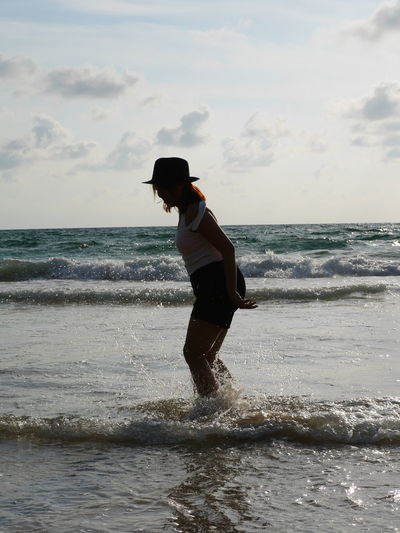 Side view of woman standing in sea against sky