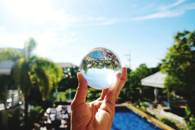 Midsection of person holding crystal ball against trees
