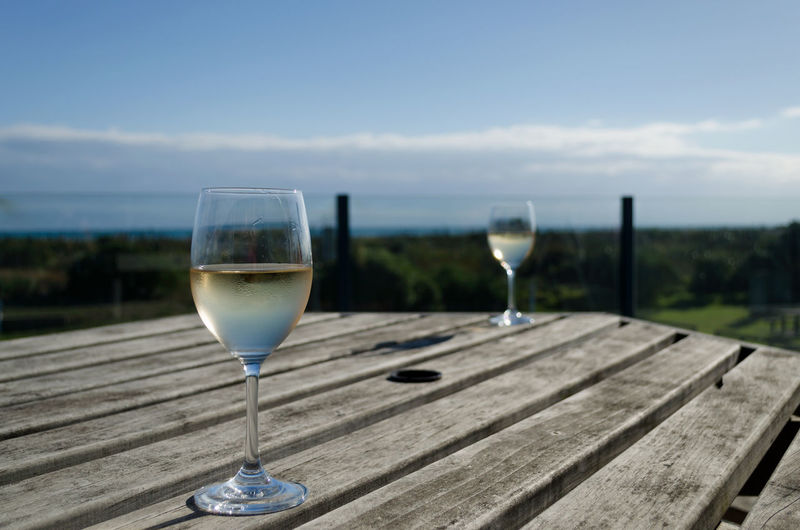 Glass of wineglass on table against sky