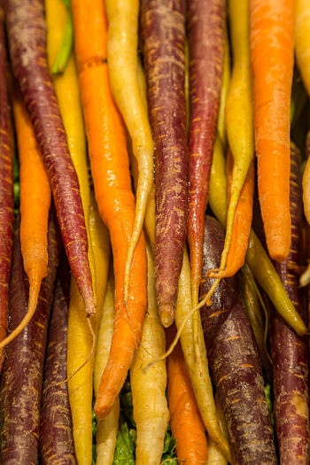 Colourful rainbow carrots for sale on a market stall