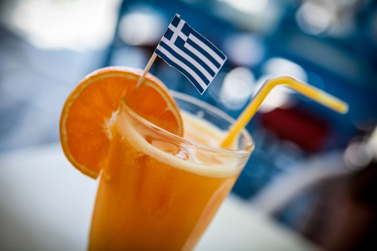 Orange juice in a glass with straw and a Greek flag Food And Drink Refreshment Drink Straw Glass Drinking Straw Close-up Fruit Drinking Glass Freshness Citrus Fruit Healthy Eating Orange Color Focus On Foreground Orange - Fruit Wellbeing Selective Focus Orange Non-alcoholic Beverage Drinking Juice Greece Flag