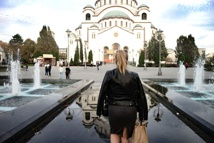 Rear view of woman standing by fountain in city