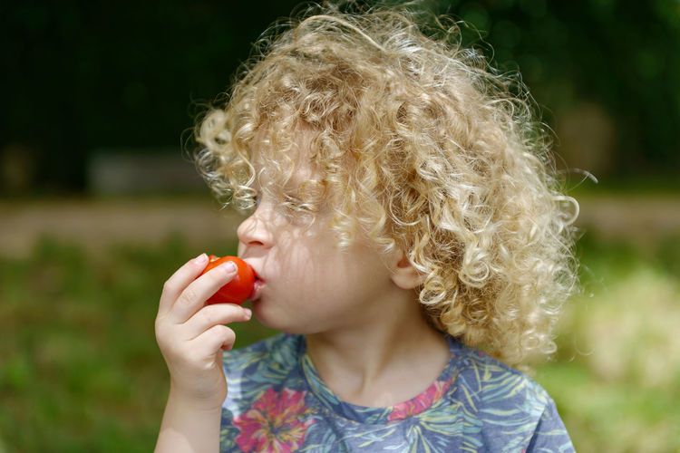 Boy With Curly Blond Hair Eating Tomato At Park