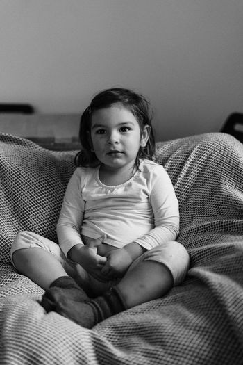 Portrait of girl sitting on sofa at home