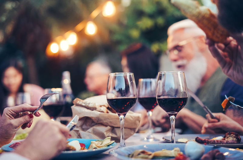 Happy family dining outdoor Happy People Friends Friendship Family Lifestyles Dinner Lunch Wine Food And Drink Drink Wineglass Adult Men Women Smiling Celebration Real People Food Holding Senior Adult Togetherness Table Red Wine Meal