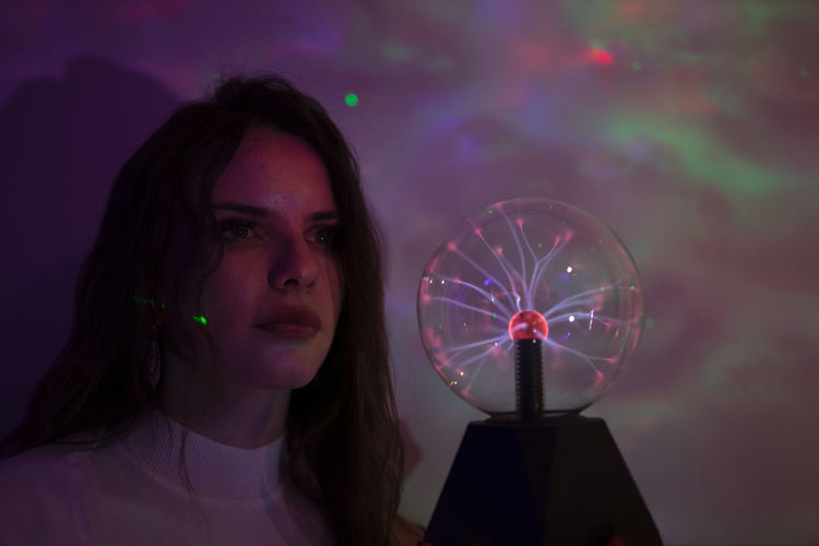 Close-up of woman holding crystal ball in illuminated room