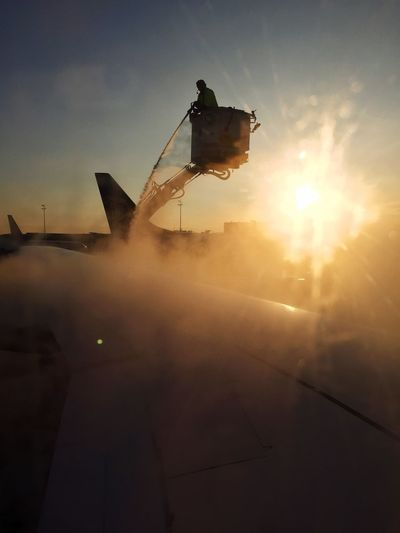 Silhouette man splashing water on aircraft wing from hydraulic platform at airport against sky