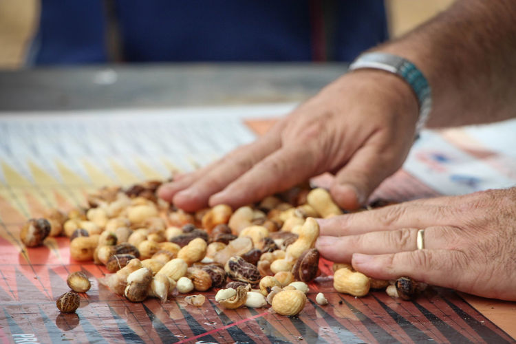 Cropped image of hand touching peanuts on table