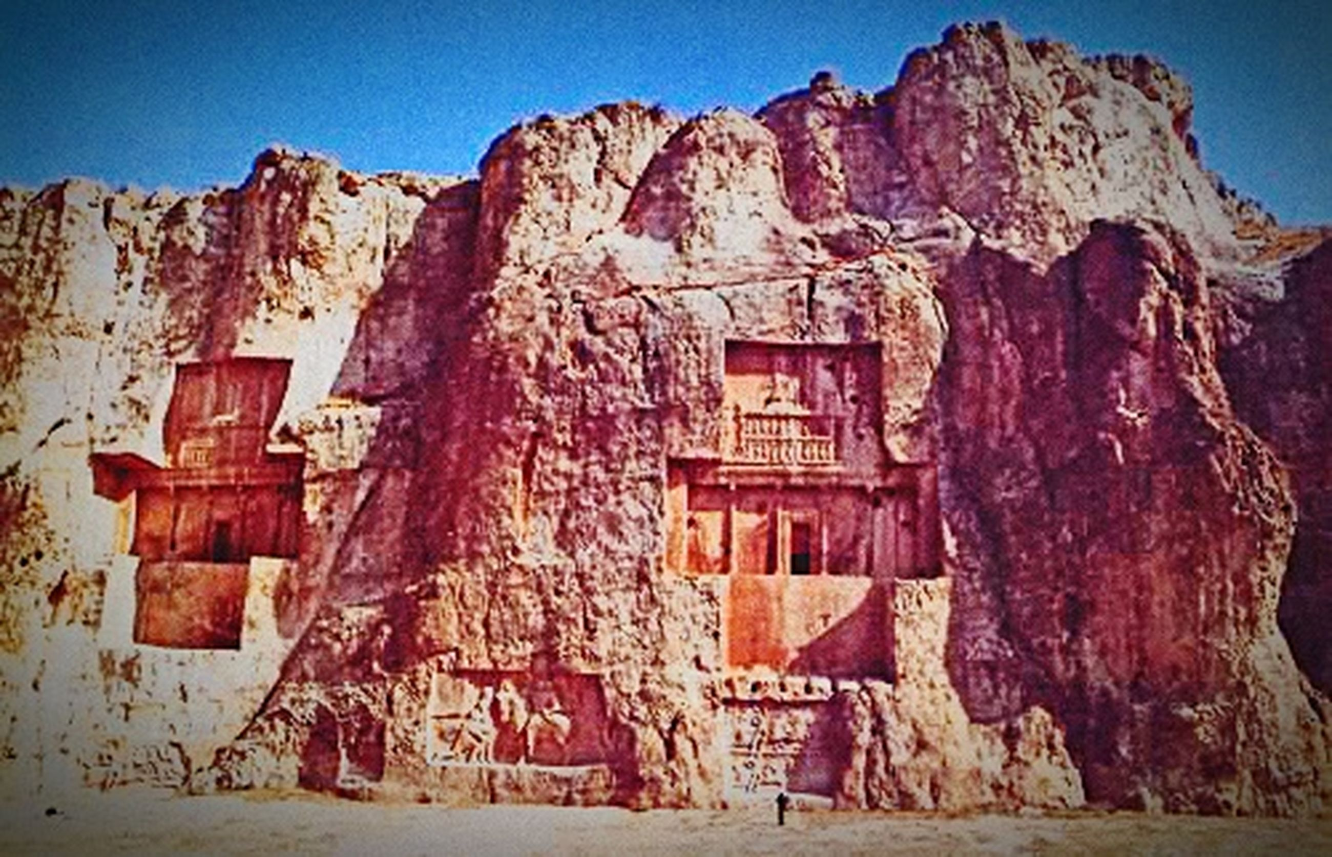rock formation, mountain, architecture, built structure, blue, clear sky, text, low angle view, rock - object, building exterior, rock, western script, abandoned, weathered, old, day, sunlight, no people, wall, outdoors