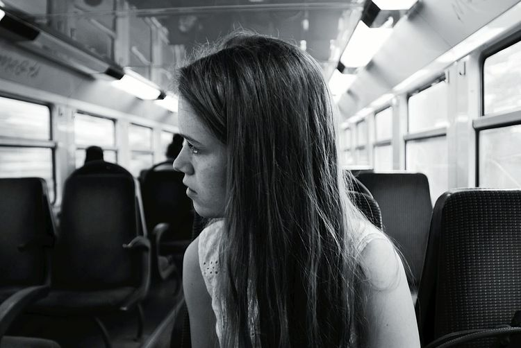 Young woman with long hair sitting in train