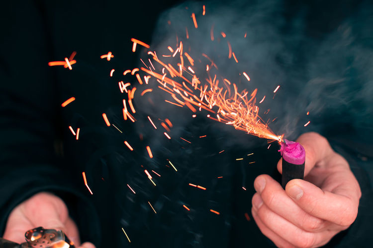 Midsection of man holding burning firecracker