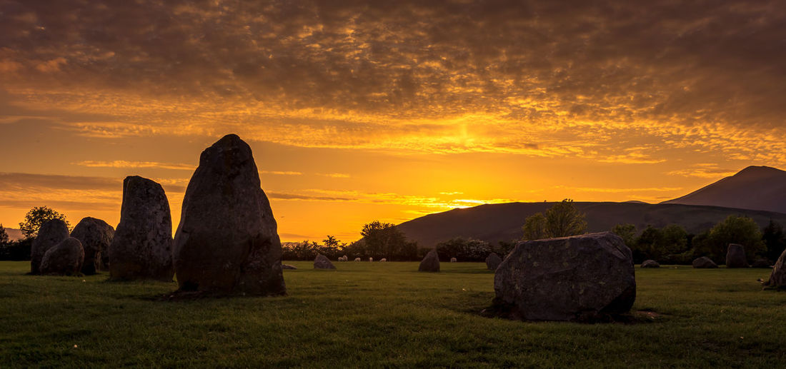 Sun setting over the ancient Castlerigg Stone Circles at Keswick, The English Lake District Acient Arquitecture Beauty In Nature Cloud - Sky Cumbria Day Dramatic Sky Grass Lake District Lake District National Park Landscape Mountain Nature No People Outdoors Scenics Sky Stone Circle Sunset Tranquil Scene Tranquility