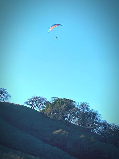 """""""Where The Wind Takes You"""" A solitary hang glider soars over a suburban open space area in unrestrained freedom save for the whim of the wind. California Hang Gliding Sky Flying Low Angle View Blue Day Mid-air Adventure Extreme Sports Paragliding Unrecognizable Person Leisure Activity One Person Sport Real People Freedom"""