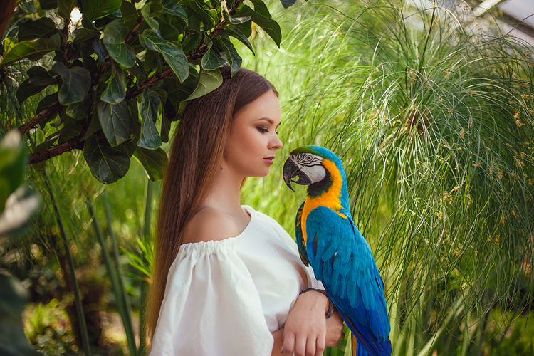 Close-up of woman with parrot