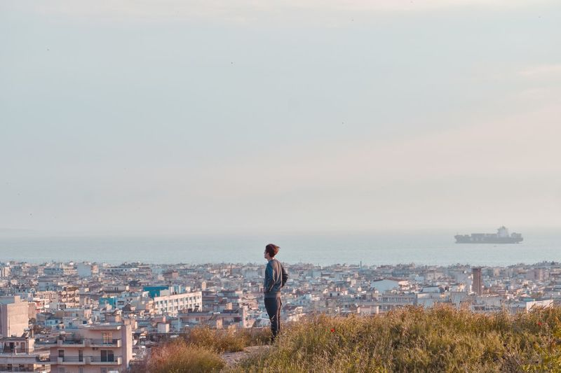 Side view of man standing against cityscape