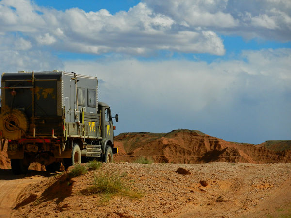 climbing a path to the top of the Flaming Cliffs (Mongolia) during a 18 month roadtrip in Europe and Asia An Eye For Travel Gobi Desert Mongolia Steyr Cloud - Sky Desert Flaming Cliffs Land Vehicle Landscape Mongolian Nature Mountain Nature Offroad Offroad Adventure Outdoors Overland Travel Overlanding Roadtrip