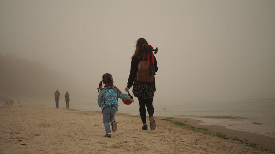 Rear view of women walking on beach