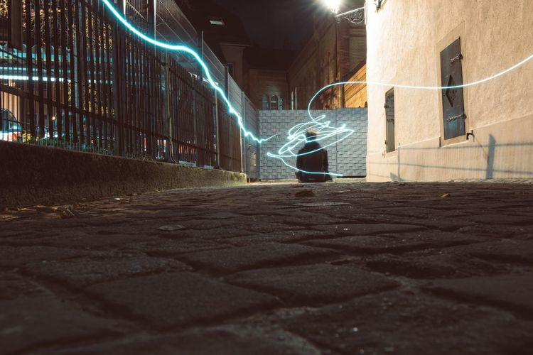 Man amidst light painting on walkway at night