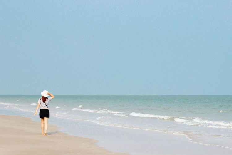 woman back walking through the beach touch the white hat with clearly blue sky, copy space Adult Ankle Deep In Water Beach Beauty In Nature Clear Sky Day Full Length Horizon Over Water Nature One Person Outdoors People Real People Rear View Sand Scenics Sea Sky Standing Tranquility Vacations Water Wave Young Adult