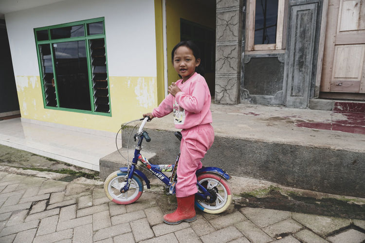 Small village girl and bicycle. Mount Bromo. Full Length One Person Childhood Child Architecture Building Exterior Real People Looking At Camera Built Structure Females Casual Clothing Bicycle Portrait Transportation Building Girls Women Smiling Outdoors Innocence Riding Bromo Vilage Little Little Girl